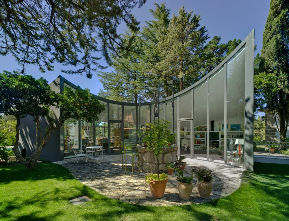 The house is surrounded by vegetation and the full-height windows allow it to bring the outdoors in