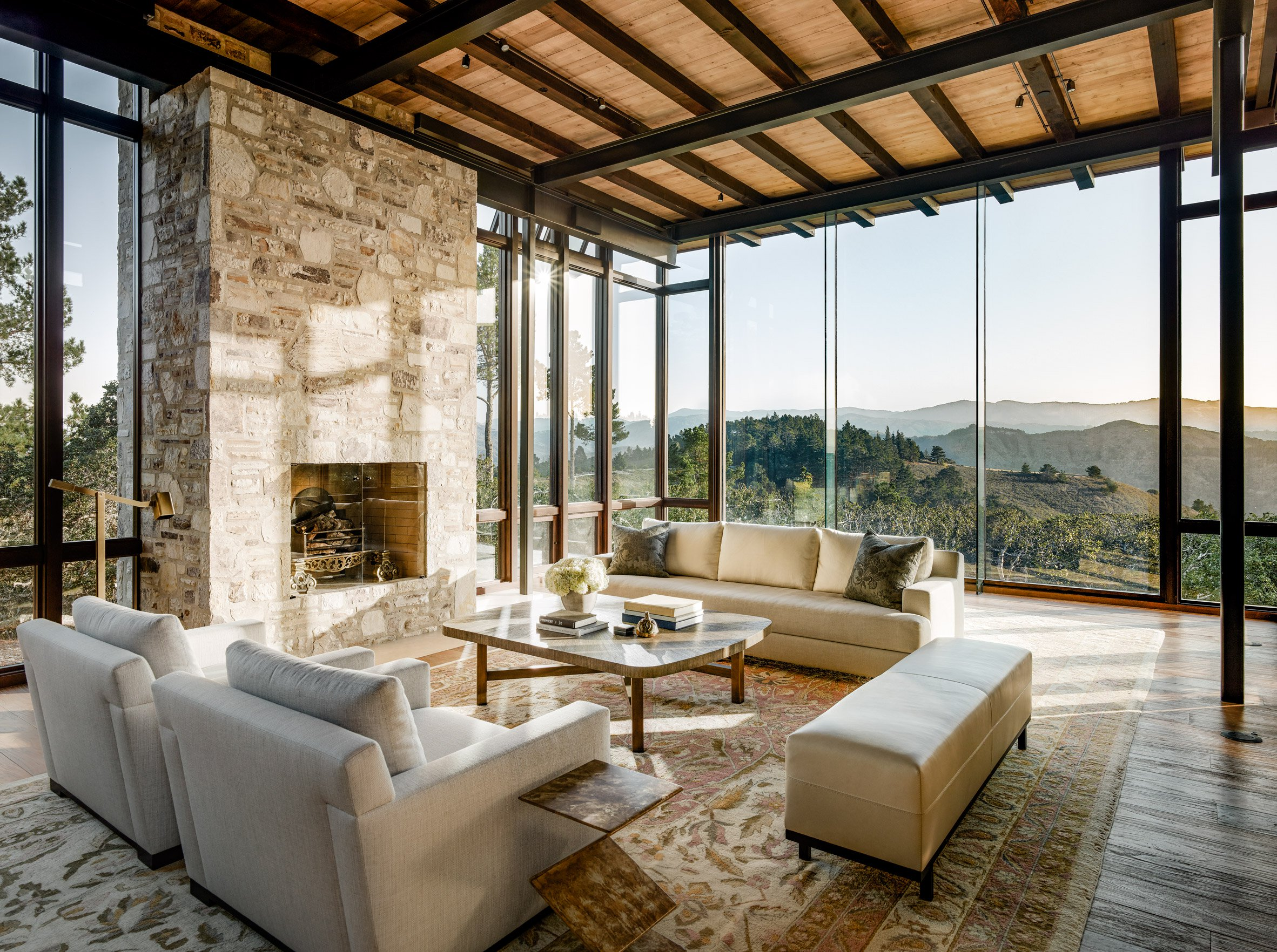A large stone fireplace with panoramic views on either side gives the living room a cozy look