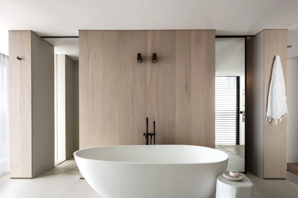 A soaking tub takes center stage in the large and open bathroom.