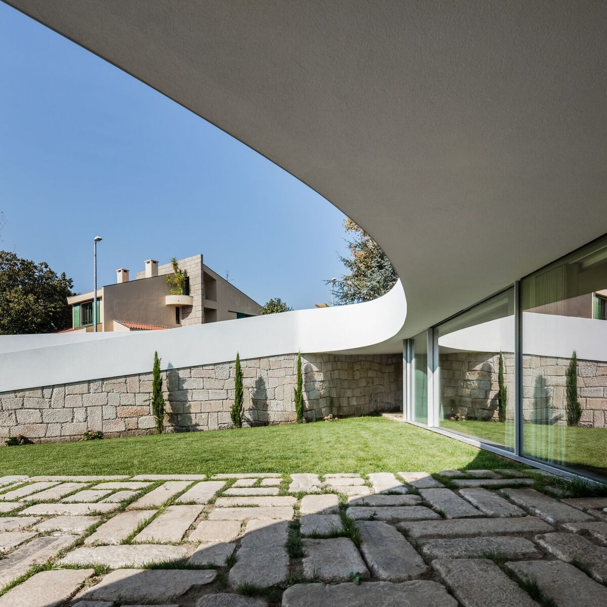 The curving shade swoops across the land creating a courtyard with a great sense of privacy