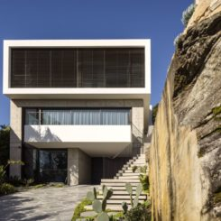 The carved-out stone boulders highlight the angular lines of the house.
