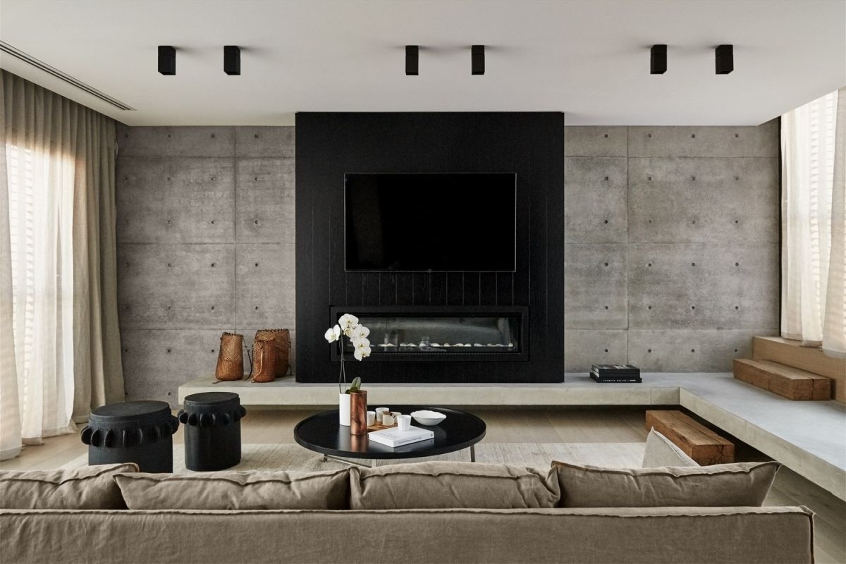 The minimalist formal living room has an industrial edge thanks to the concrete and ceiling lights.