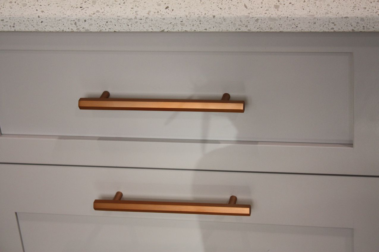 Coppery rose gold hardware adds warmth to the gray cabinetry.