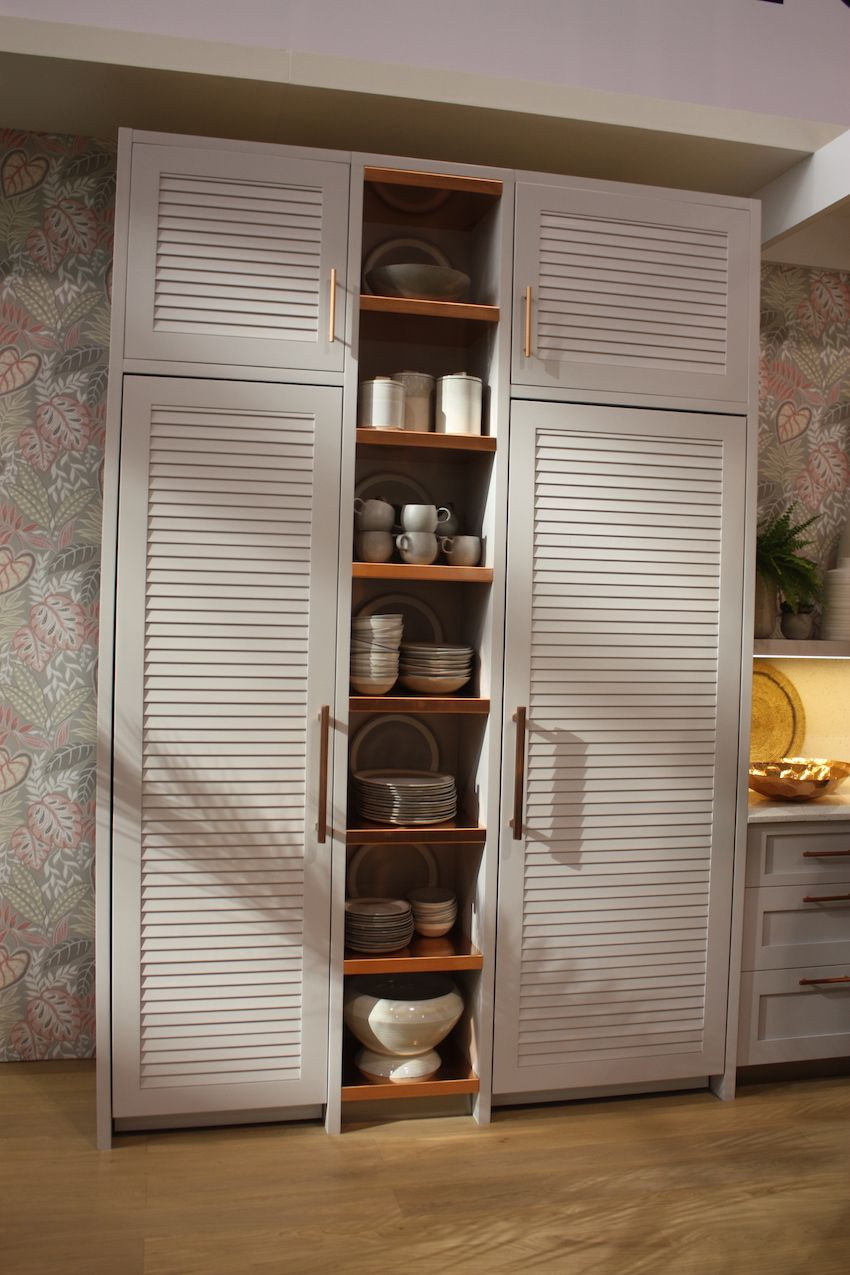 The warm wood of the open shelving mimics the rose gold of the hardware.