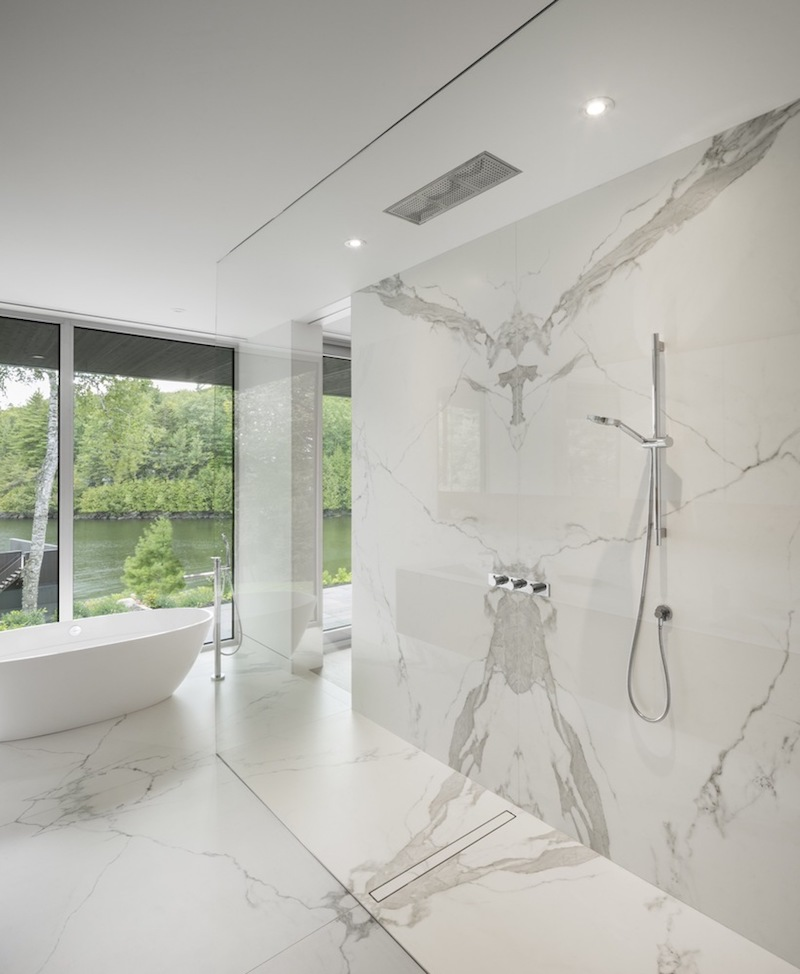 Clear glass dividers frame the shower, allowing it to become an integral part of the room's stylish decor
