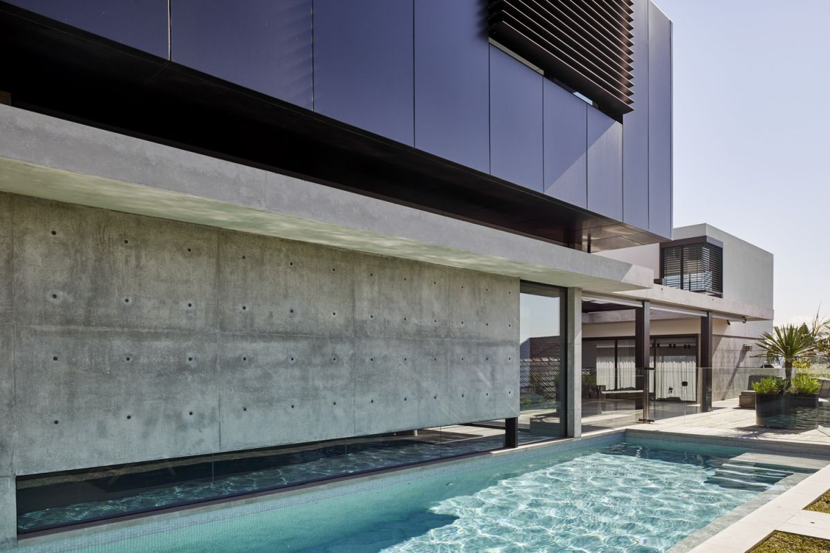 The pool runs along the side of the house, bounded by a glass wall.