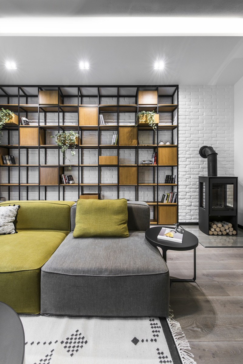 A large shelving unit with a metal frame and wooden cubbies occupies one of the walls