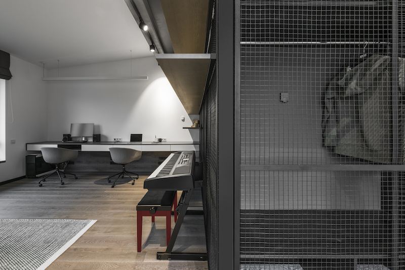 The office has two workspaces combined into a single minimalist desk with two chairs