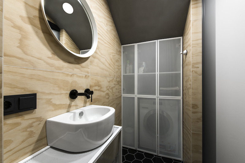 A dividing panel conceals the washing machine and storage shelves