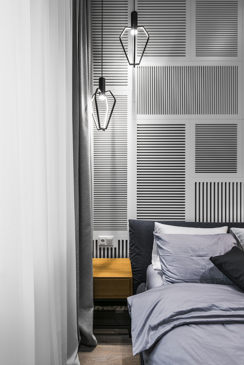One of the bedroom walls is decorated with white-painted shutter panels of different shapes and sizes