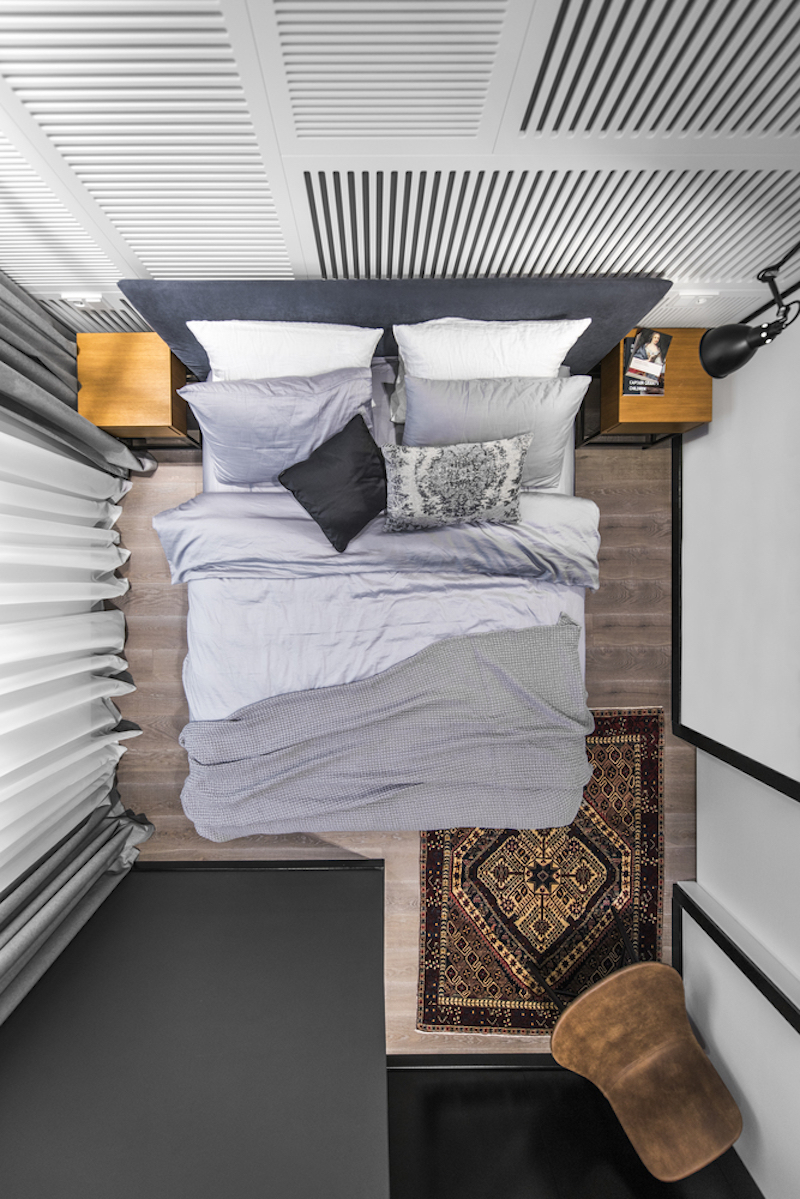 Even though the bedroom is tiny, its high ceiling prevents it from feeling too cluttered