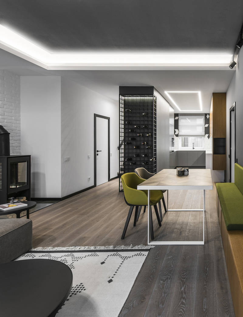 The living and dining area are on one side of the volume and the kitchen is on the other