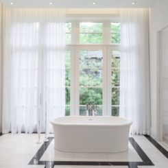 White bathroom with freestanding tub and curtains