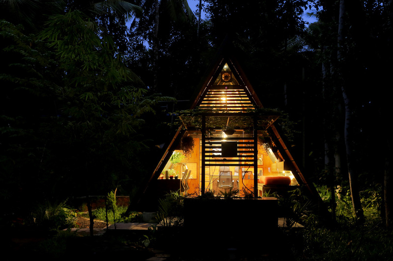 The cabin's triangular structure is most noticeable at night when the lights are on and the A-frame is highlighted