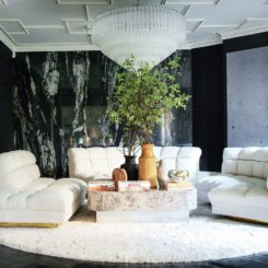 Beautiful living room by Caroline Legrand Design featuring white sofa and marble walls