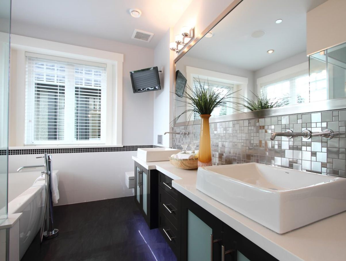 This bathroom backsplash is neatly framed by the counter and by the extra long wall mirror