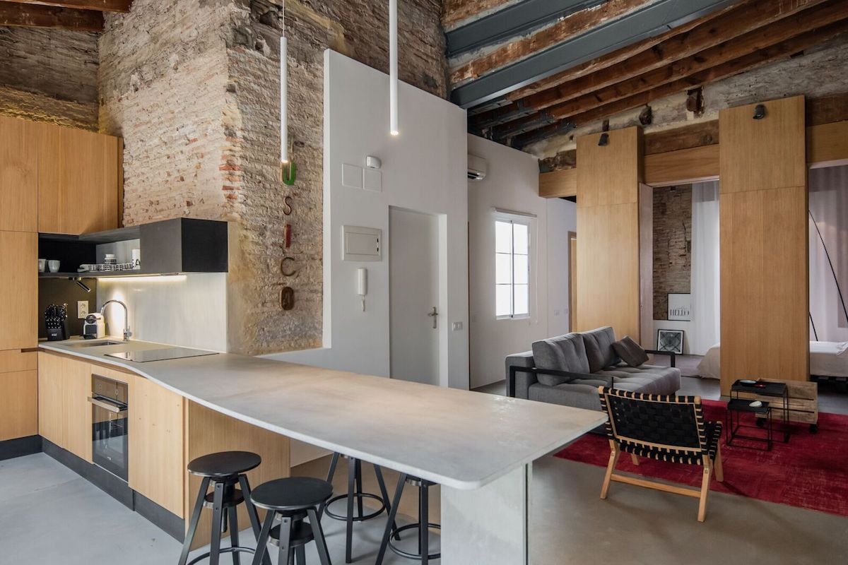 The apartment has an open floor plan living space with exposed brick walls and ceiling beams