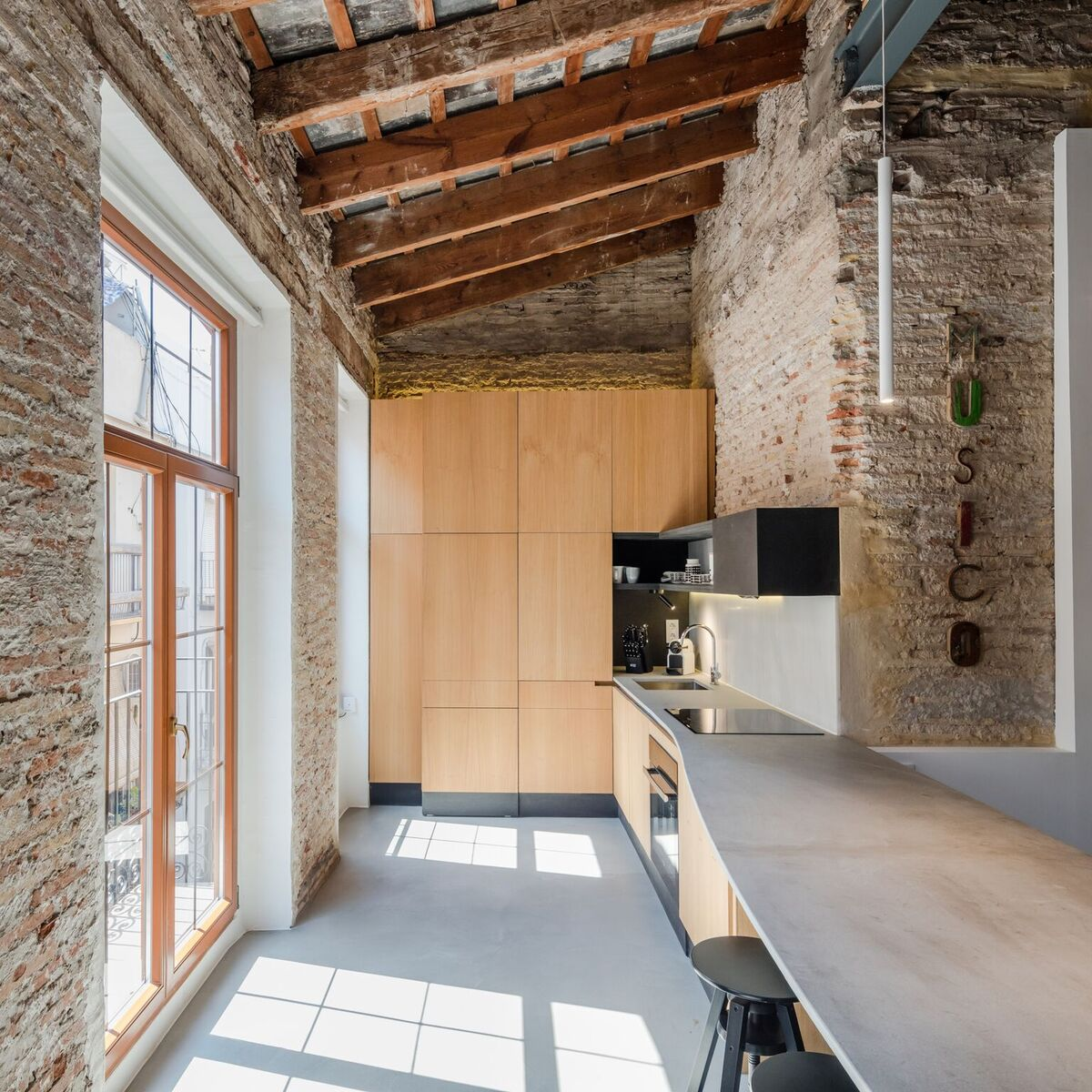 The kitchen is naturally embedded into the space, taking advantage from all the natural light that enters the apartment