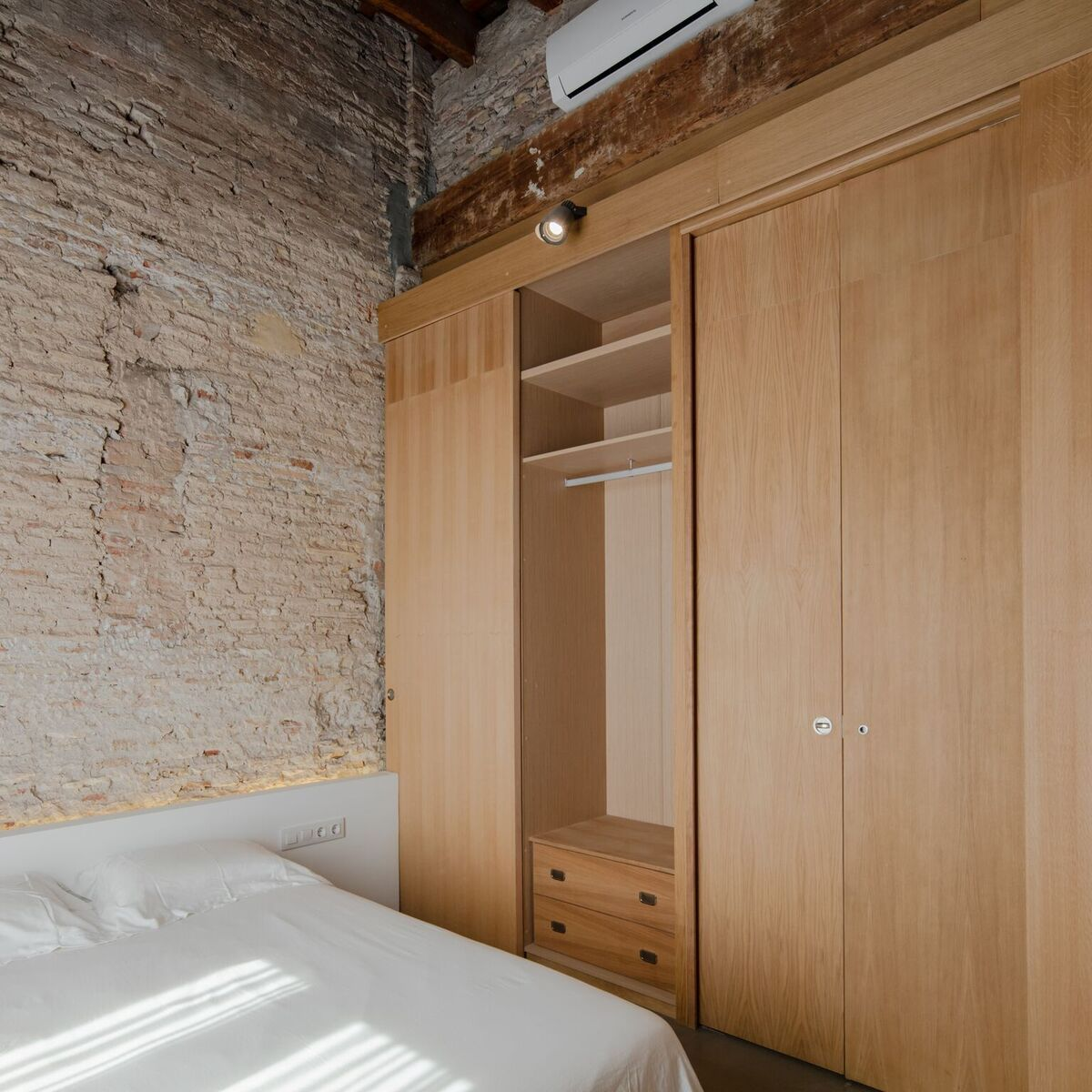 These partitions are made of wood and serve multiple purposes. Here you can see one being used as a wardrobe