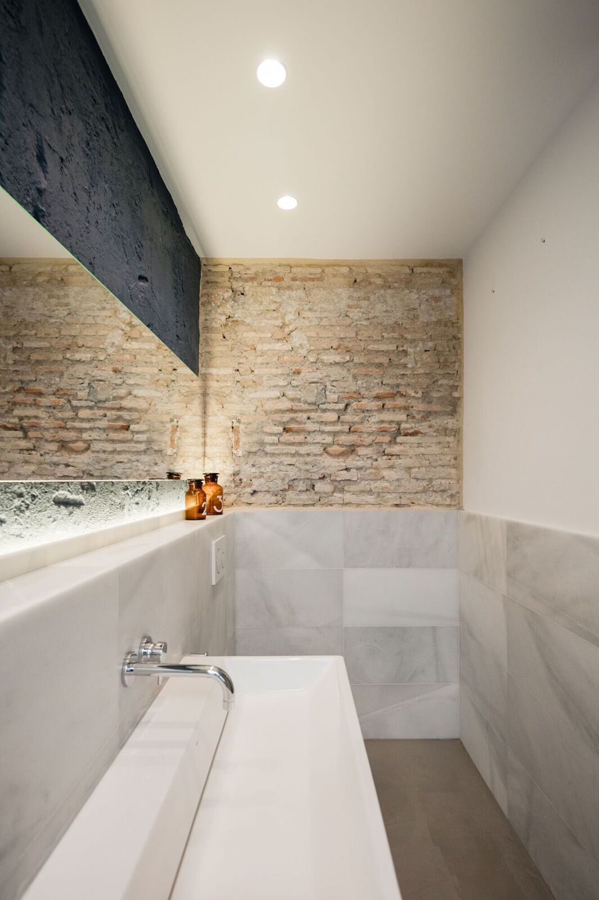 The brick walls are one of the elements which unify the internal spaces, bathroom included