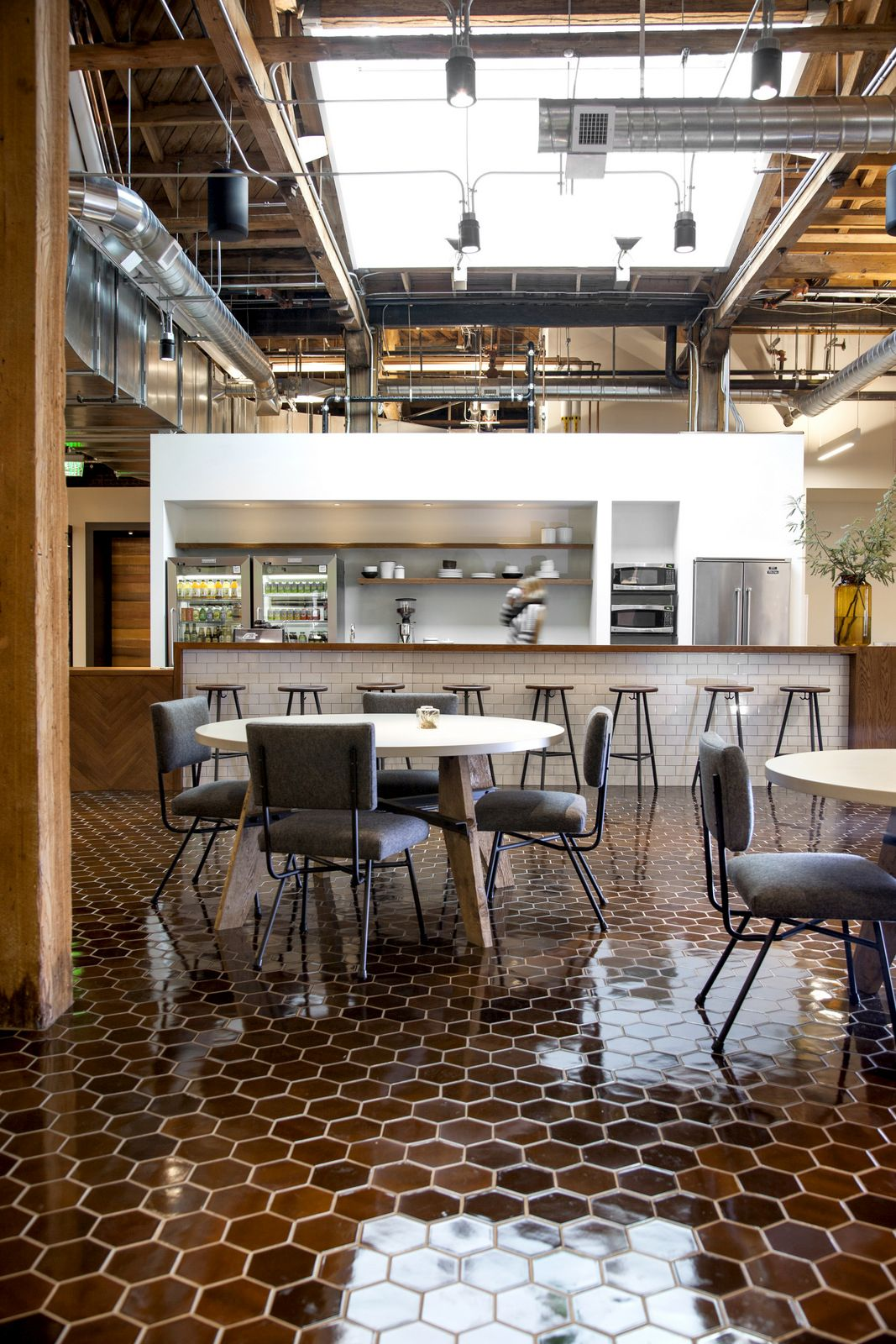 One of the workspaces is a casual and open coffee shop/ cafeteria style space with a high ceiling and tiled floor