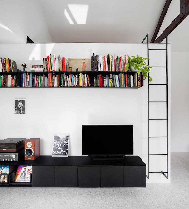 There's also a metal shelf for books placed upper on the wall above the media unit