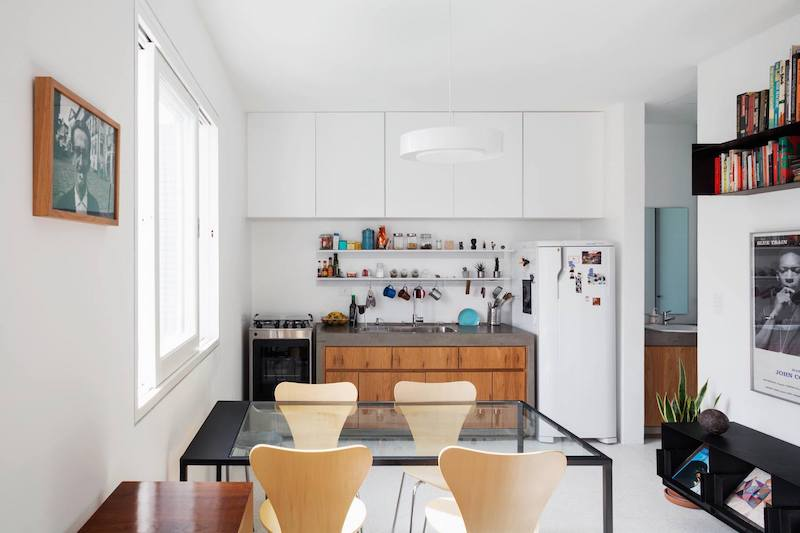 The kitchen is open and neatly packed with storage cabinets and two sleek wall shelves