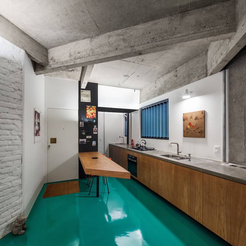The green floor extends in all the different areas of the apartment including the kitchen