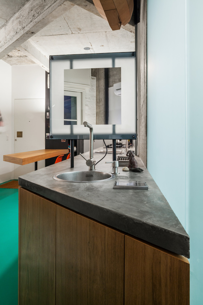 The concrete countertop adds a subtle industrial touch to the kitchen and shares a strong connection with the kitchen
