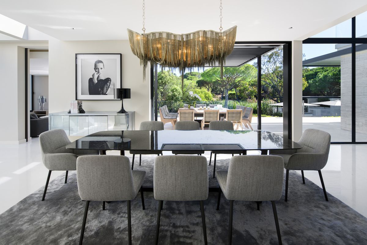 The chandelier hanging above the dining table gives the space a luxurious and sophisticated look