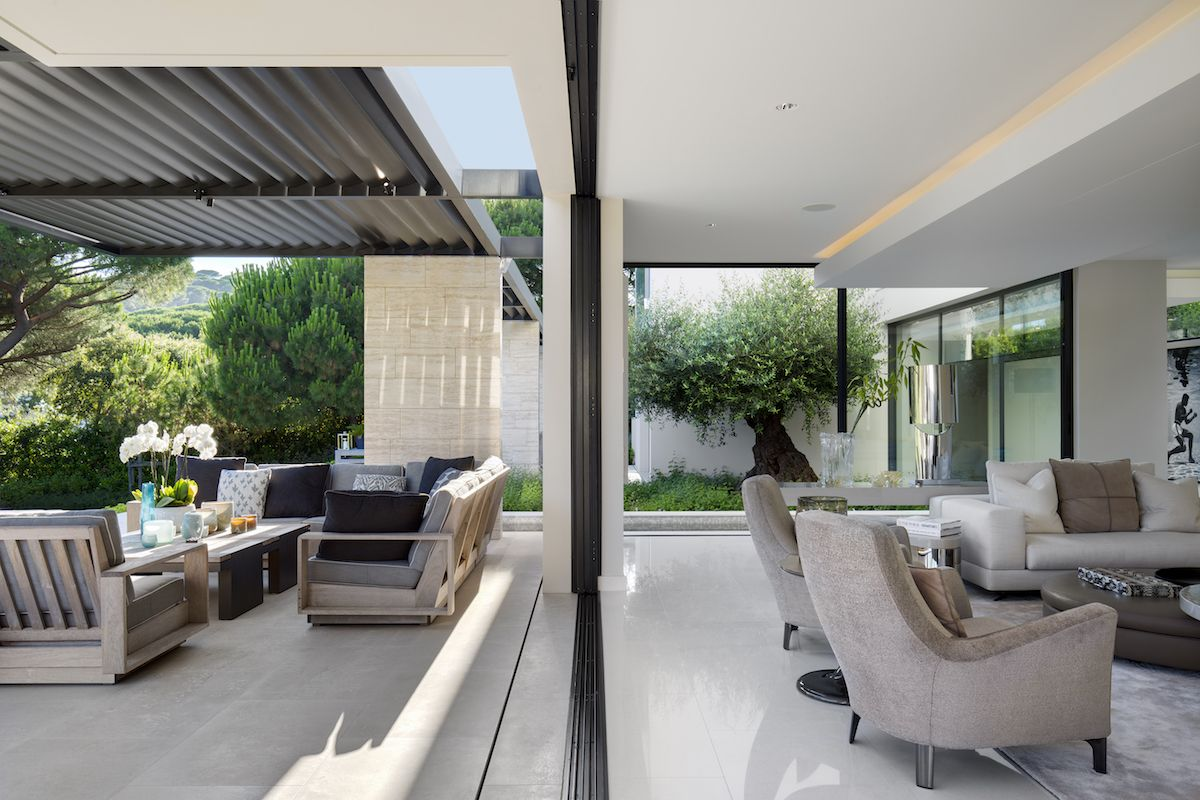 The social spaces of the house have a very close connection with the outdoors, featuring sliding glass doors and frameless windows