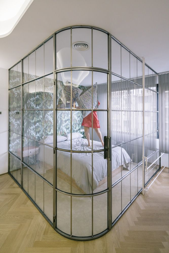 The bedroom is defined by the wall covering as well as the curved glass wall.