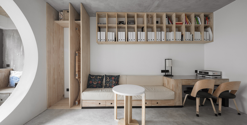 The new living area has a custom wall unit which combines a sofa, a desk and a storage cabinet