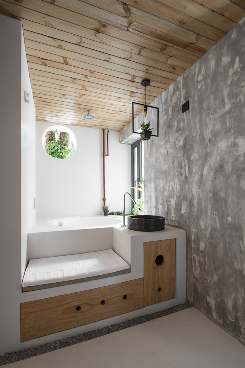 The bathroom has been relocated and redesigned. It now incorporates a tub built into a platform