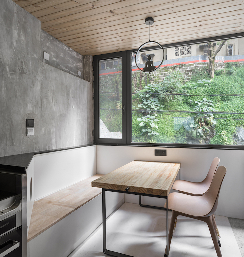 The dining area is a cozy little nook with a bench and a simple table right next to the window