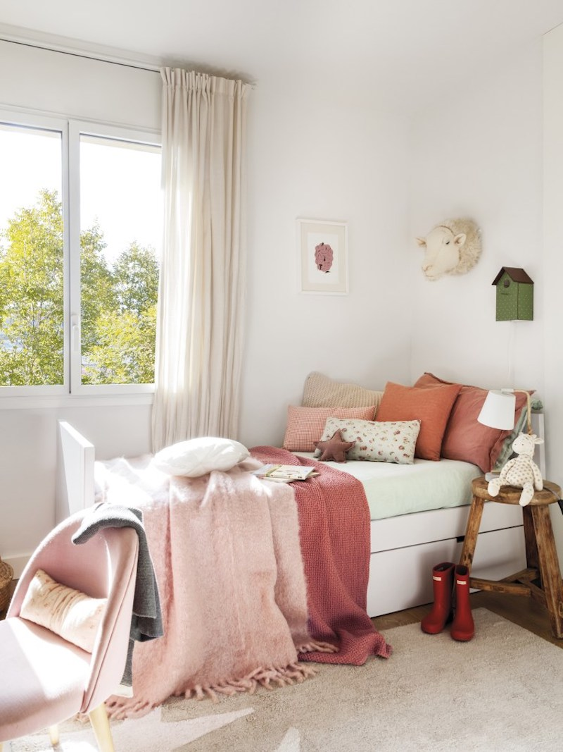 The little girl's bedroom is decorated with tones of pink and soft pastels in the same manner as the rest of the spaces