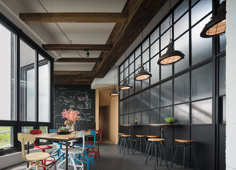 One of the two zones inside the building is a cafe and its interior design has prominent industrial details