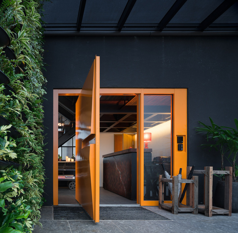 One of the entrances features a large pivot door in an orange-brown shade which contrasts with the black facade