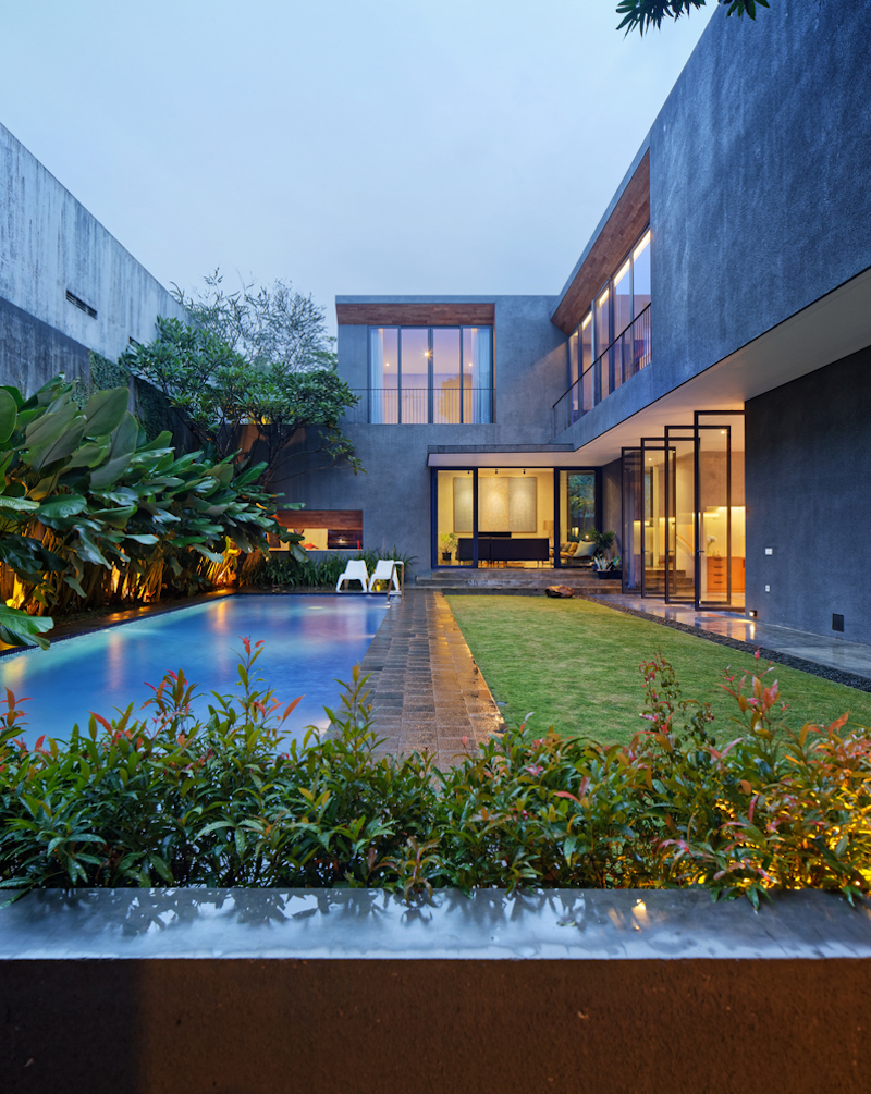 The swimming pool area is framed by concrete volumes on three sides, enjoying a high degree of privacy