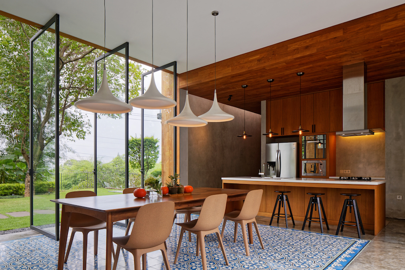 The dining area is part of a large open floor plan but is neatly delineated by the patterned floor tiles