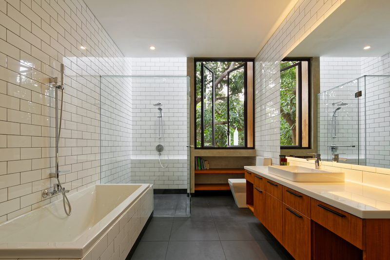 Warm wood accents give the bathrooms a welcoming appearance, complementing the tiled walls and floors
