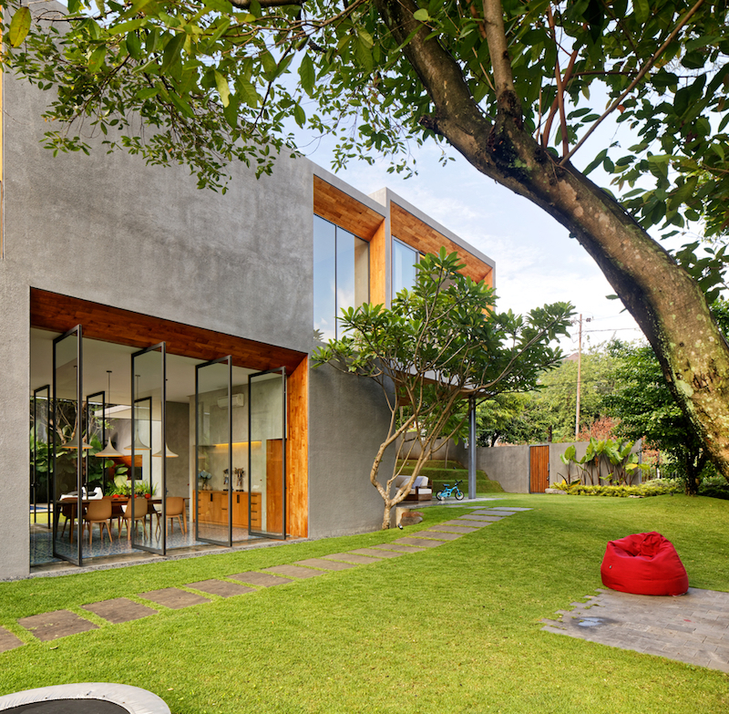 The exterior walls of the house are clad in grey concrete and they contrast beautifully with the wood-lined openings