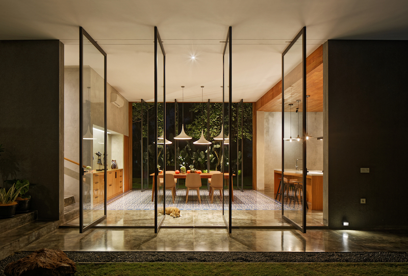 A series of tall pivot doors made of glass open up the dining area to the yard and bring in lots of natural light