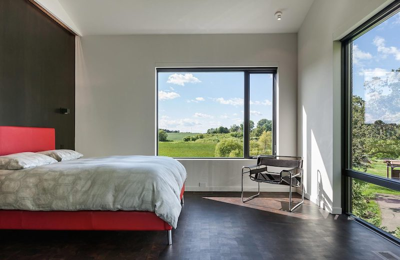 The master bedroom has large windows on two different sides and offers views in two directions