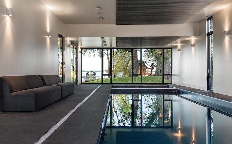 An indoor swimming pool on the ground floor features a cozy lounge space and direct access to the garden