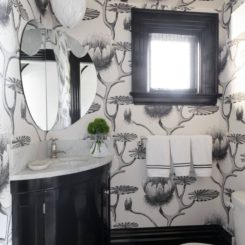 Powder room with black and white wallpaper and corner vanity