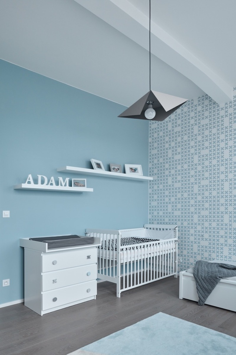 The nursery room is the only space with colored walls, featuring a pastel blue-themed interior decor