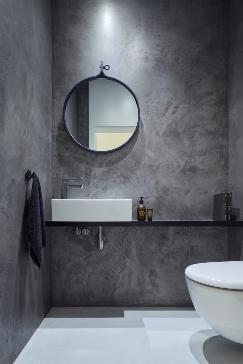 The round wall-mounted mirror complements the minimalist shelf vanity and the rectangular washbasin