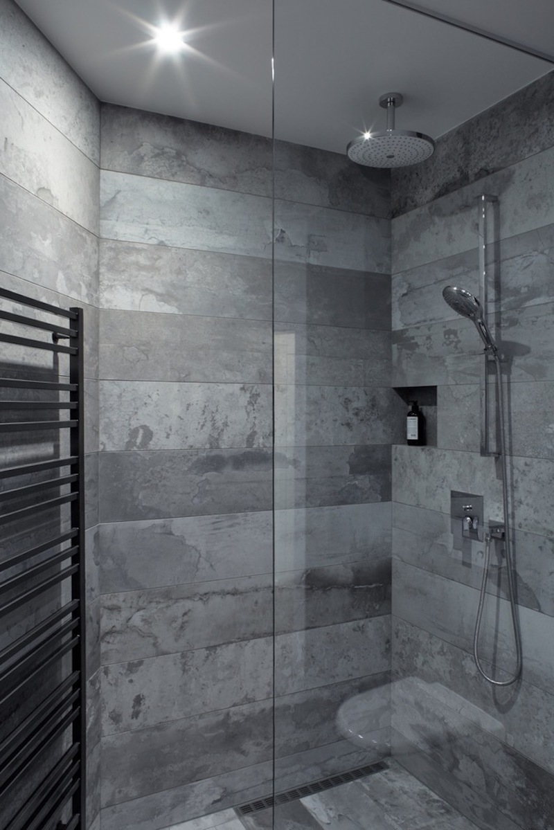The walk-in shower features a clear glass wall and a built-in wall niche for convenient storage