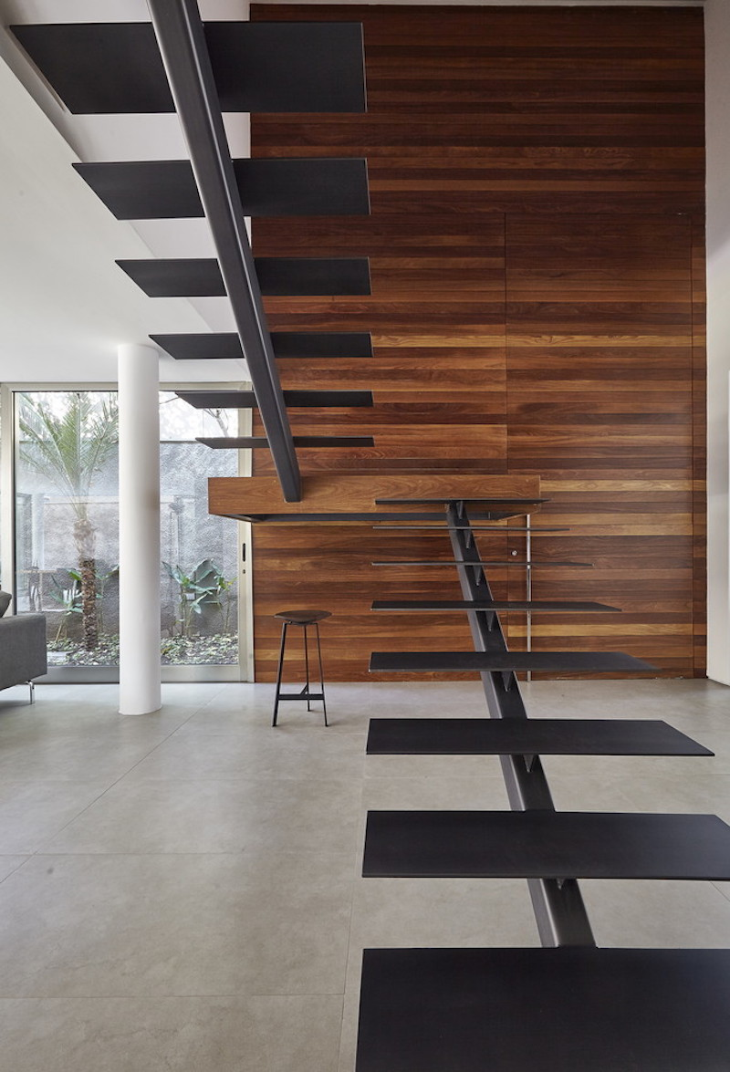 The staircase introduces metal into the decor and is balanced out by a wood-paneled accent wall